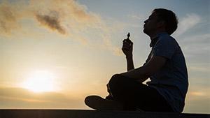 A man vaping marijuana at sunset
