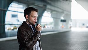 man vaping using an e-cigarette device